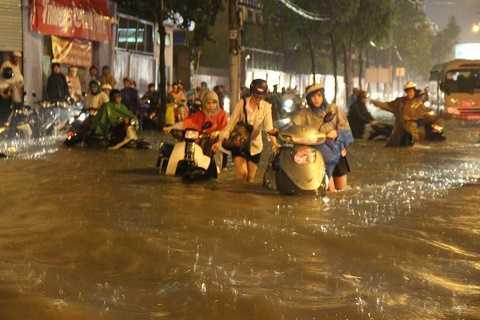 Nhiều ô tô và xe máy chết máy trên đường trong mưa ngập.