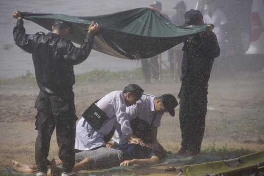 Lực lượng CSCĐ đứng che mưa để các bác sĩ sơ cứu người bị nạn khi bão đang đổ bộ