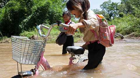Tranh thủ ngày nắng, em Sùng Thị Muội (học sinh lớp 4 Trường tiểu học Mạc Thị Bưởi) dắt xe qua suối để 'tiết kiệm' 2km đường vòng tới trường