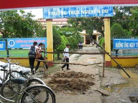 Các em HS Trường THCS Nguyễn Du phải chen qua hàng rào để vào trường học