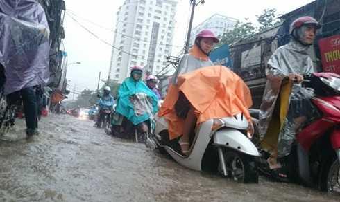 Người tham gia giao thông vất vả vượt qua biển nước tại phố Định Công (Ảnh: Việt Linh)