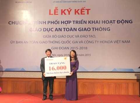 Thứ trưởng Bộ GD-ĐT Nguyễn Thị Nghĩa (bên phải) nhận 16.000 mũ bảo hiểm đạt chuẩn do Honda trao tặng học sinh nhân dịp năm học mới