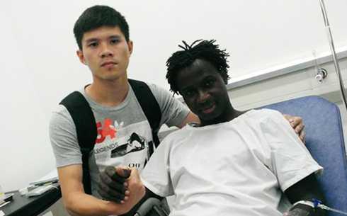 Trung vệ Dương Thanh Hào (trái) đến xin lỗi và động viên Abass trước khi đồng nghiệp lên bàn mổ.