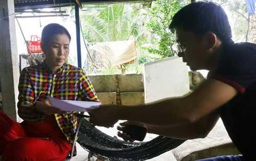 Chị Nguyễn Thị Kim Phương - vợ ngư dân Ngô Văn Sinh - ký đơn nhờ luật sư khởi kiện - Ảnh: K.Nam