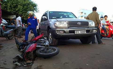 Chiếc xe máy màu đỏ bị tông văng lề đường