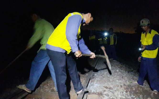 Anh em Đội Quản lý đường sắt Bình Thuận (thuộc Công ty Quản lý đường sắt Sài Gòn) gia cố lại đoạn đường ray bị hất văng khỏi hệ thống đường ray lúc 0g15 sáng 30-9 - Ảnh: NGUYỄN NAM