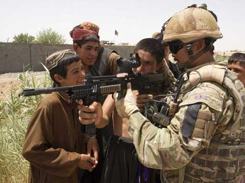 Hạ sĩ quân đội Anh Birendra Limbu cầm khẩu súng trường bên đứa trẻ Afghanistan ở khu vực trạm kiểm soát bên ngoài thị trấn Lashkar Gah, tỉnh Helmand, miền Nam Afghanistan, 13/7/2011.