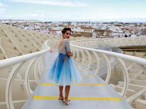 Một người mẫu đang đứng trên cầu đi bộ cấu trúc bằng gỗ Metropol Parasol, Tây Ban Nha