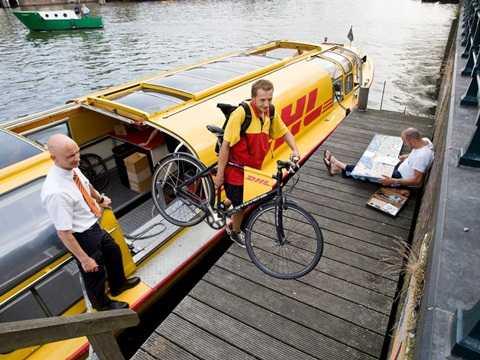 Con tàu chuyên chở đồ phát nhanh qua các kênh rạch của thành phố Amsterdam