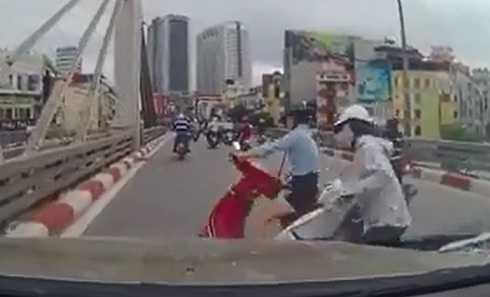 Do người đi trước phanh bất ngờ, hai người phụ nữ đi xe tay ga không kịp xử lý, ngã xuống trước đầu xe ô tô