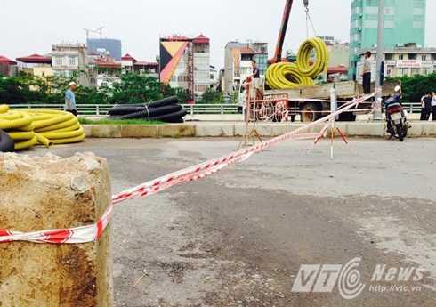 Vị trí đường dẫn lên cây cầu cạn đang thi công dở được cảnh báo sơ sài. Dây cảnh báo được buộc tạm vào cột bê tông