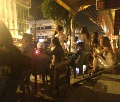 Nhiều cô gái váy ngắn, ăn mặc hở hang ra ngồi vỉa hè sau khi bị kiểm tra hành chính. Ảnh: Phan Cường