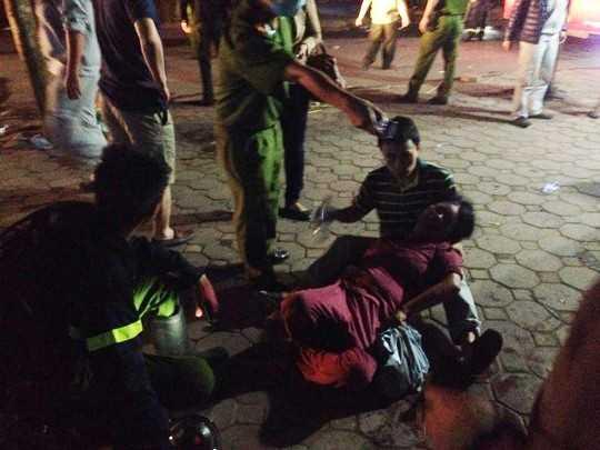 Người dân và lực lượng cứu hộ sơ cứu người bị ngạt khói. Ảnh: Người lao động.