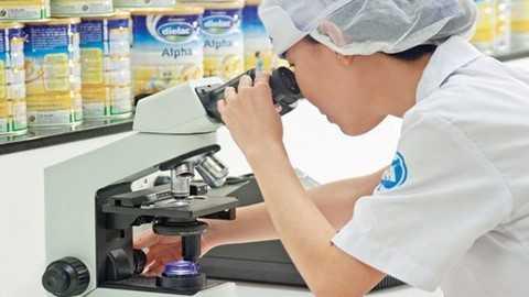 Nhà máy sữa bột Việt Nam (ảnh trên) và nhân viên trong phòng thí nghiệm