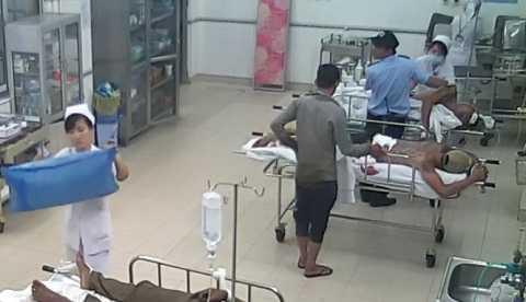 Đối tượng (áo xám) đến bên giường Hưng vờ như thăm bệnh nhân. Ảnh trích từ video clip