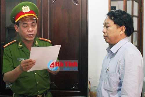 Nguyên Chủ tịch UBND huyện Ky Anh (phải) nghe đọc lệnh khởi tố Ảnh: Báo Hà Tĩnh