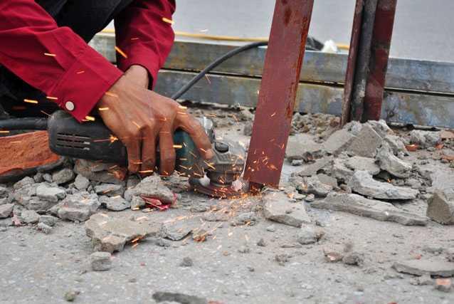 Những thanh sắt đóng sâu xuống lòng đường khiến công nhân phải dùng máy cắt sắt cắt sát mặt đường để đảm bảo an toàn cho người tham gia giao thông.