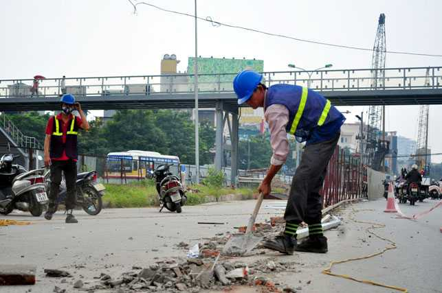 Công nhân dọn dẹp gạch, vữa rơi vãi trên đường để đảm bảo an toàn cho người đi đường.