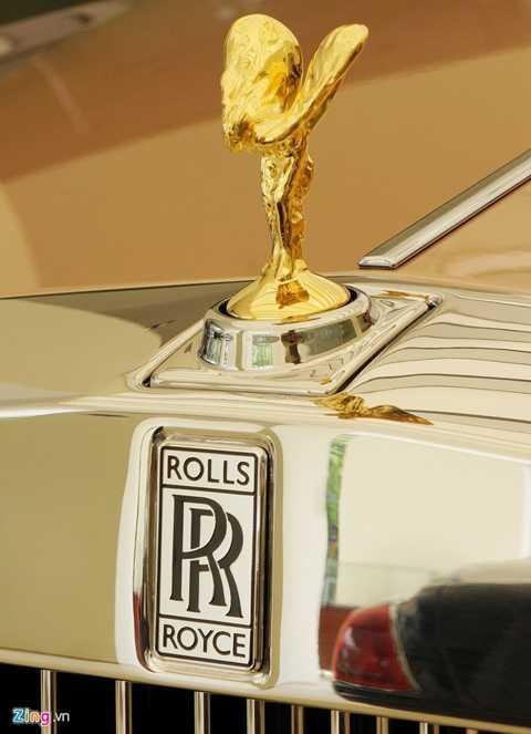 Rolls-Royce Phantom Lửa Thiêng nổi bật với ngoại thất 2 tông màu vàng hồng và đỏ rượu vang Tây Ban Nha. Logo biểu tượng Spirit of Ecstasy còn được mạ vàng.