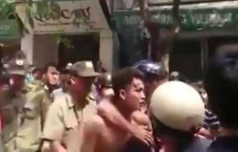 Tài xế taxi bị một số người dân lột áo, hành hung.
