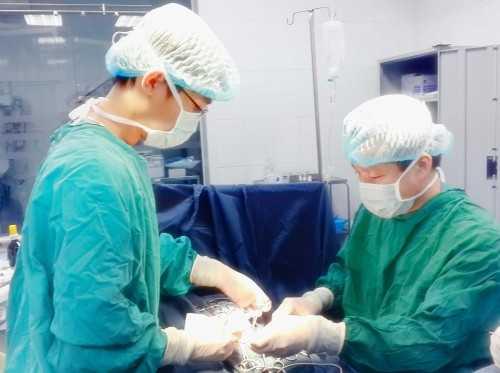 PGS. TS Trần Ngọc Sơn, Phó trưởng khoa Ngoại (bên phải) phẫu thuật viên chính thực hiện ca mổ cho bé Bình.