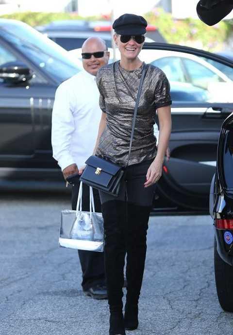 Laeticia Hallyday mặc áo kiểu bất đối xứng ánh nhũ, quần jeans skinny và bốt da lộn cao qua gối khi đi đến Meche Salon ở Beverly Hills.