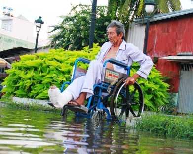 Người đàn ông đi xe lăn không thể tự về nhà vì nước lên quá nhanh.