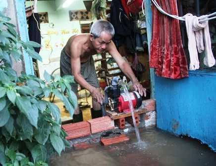 Người đàn ông bơm nước từ trong nhà ra ngoài đường.