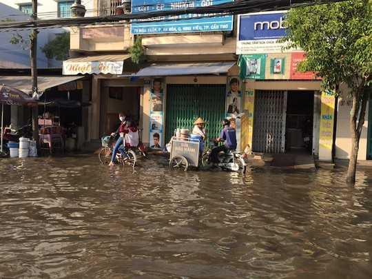 Nước ngập đầy đường, tràn cả vào nhà dân, gây khó khăn cho việc mua bán, sinh hoạt.