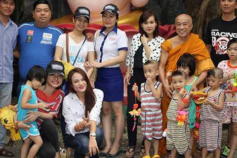 Nữ ca sĩ hạnh phúc lưu giữ kỉ niệm cùng các em nhỏ và sư thầy trụ trì của chùa Kỳ Quang.