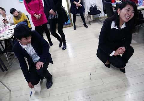 Học viên trong lớp đào tạo quý tộc đang học cách nhặt đồ bị rơi xuống sàn