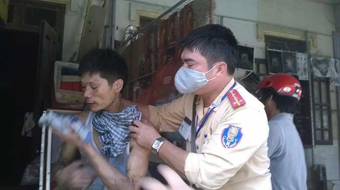 Lực lượng chức năng ngăn người đàn ông chuẩn bị lao vào đám cháy cứu tài sản - Ảnh: Duy Ngợi