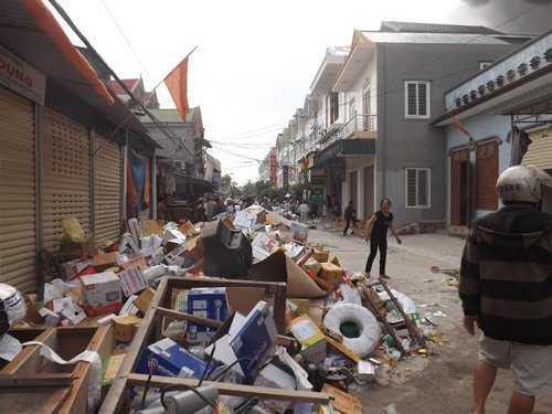 Người dân cố gắng vận chuyển hàng hóa ra bên ngoài tránh tổn thất (Ảnh: Dân Việt)
