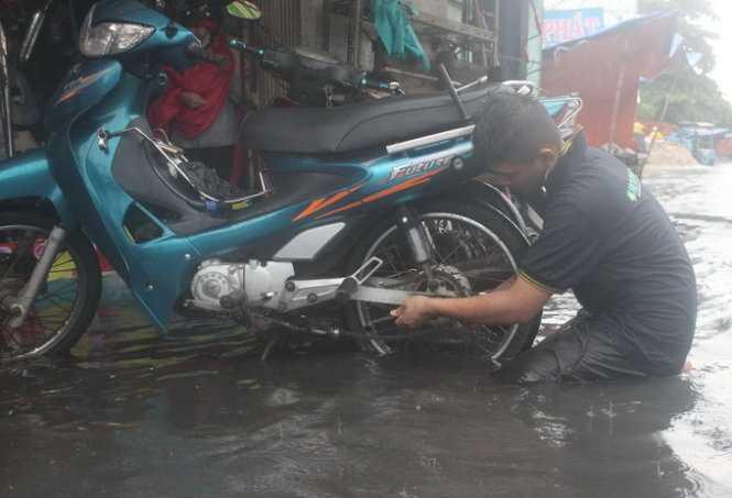 Một thợ sửa xe chết máy trên đường An Dương Vương (Ảnh: Đức Phú)