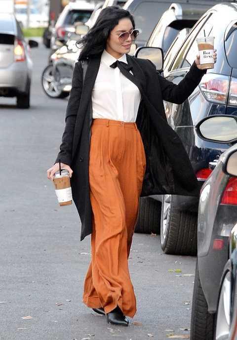 Vanessa Hudgens thu hút mọi ống kính của paparazzi khi dạo phố West Hollywood. Cô nàng tạm gác phong các boho quen thuộc mà thay bằng bộ đồ thanh lịch: áo sơ-mi trắng cột nơ, quần palazzo cam và áo khoác dạ xám.