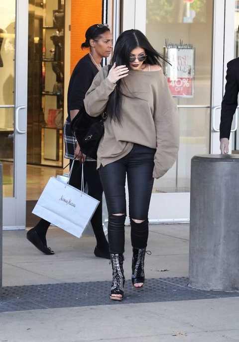 Kylie Jenner bụi bặm khi mua sắm ở New Rolls Royce với áo sweater oversize và quần jeans skinny rách, bốt cột dây hở mũi.