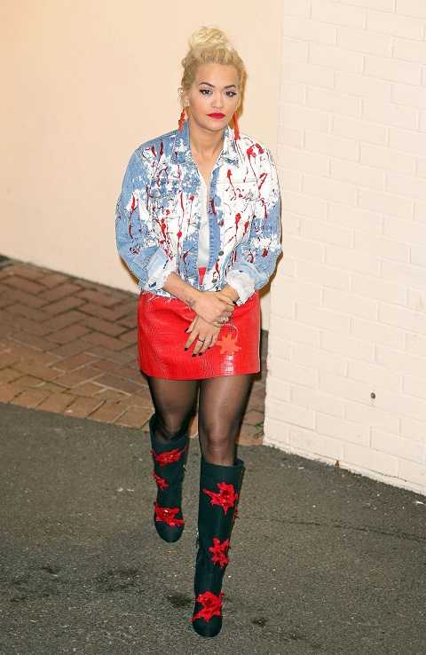 Rita Ora năng động trong set đồ: áo khoác jean, váy da và bốt cao tới gối tại London tuần qua.
