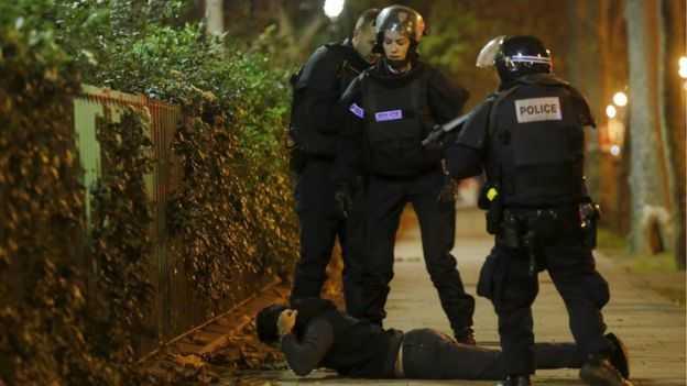Cảnh sát chặn một người đàn ông để kiểm tra bên ngoài hiện trường khủng bố