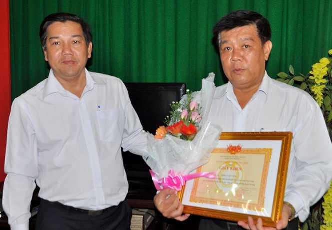 Ông Trịnh Minh Tự trao giấy khen và hoa cho ông Tống Văn Viên (phải) - Ảnh: Đức Thành
