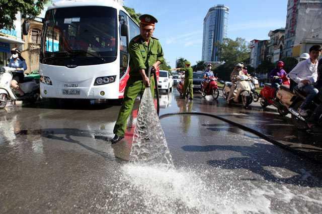 Công an tham gia rửa sạch bùn đất trên đường Trần Duy Hưng.