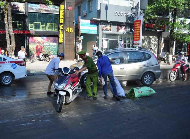 Lực lượng chức năng ra giúp người dân dựng lại xe.