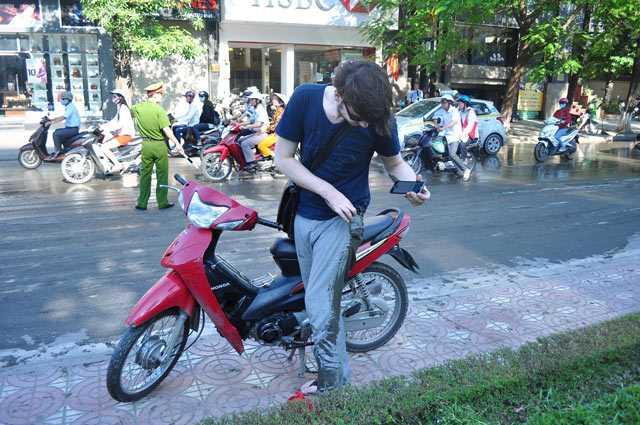 Bị ngã xuống đường, một du khách người nước ngoài bẩn hết quần áo.