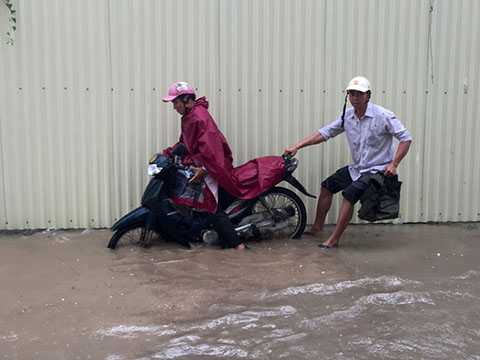 Một số người điều khiển xe máy đã bị ngã ra đường khi đi qua đoạn đường ngập.