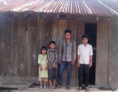 Y Pháo Byă cùng các em trước căn nhà tạm bợ