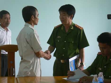 Đại tá Phạm Thật bắt tay công  dân Huỳnh Văn Nén sau khi công bố, trao quyết định đình chỉ bị can. Ảnh: Phương Nam