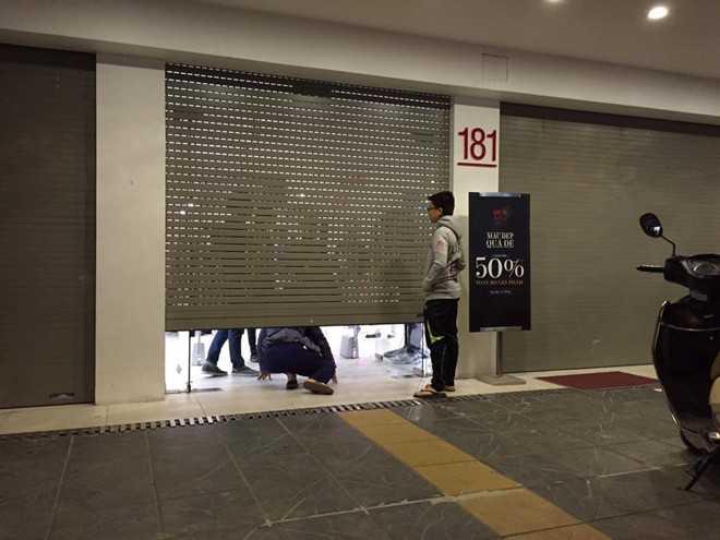 Trong ảnh là một khách hàng cố chui qua cửa sếp đã khép để vào mua hàng giảm giá tại một cửa hiệu trên đường Giảng Võ (Hà Nội). Ảnh: Khánh Linh.