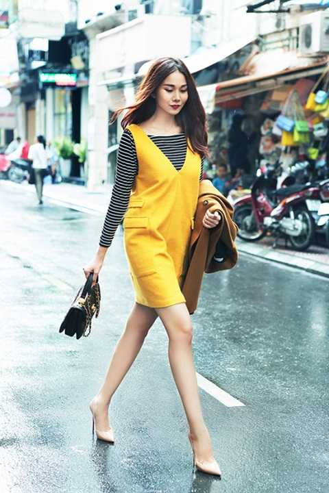 Thanh Hằngnổi bật trên phố trong ngày mưa u ám với chiếc đầm dạ vàng mix với áo thun sọc ngang vừa thanh lịch vừa khỏe khoắn.