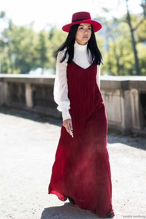 Đầm dây maxi màu đỏ thướt tha được cô nàng phối với áo xuyên thấu trắng cùng mũ fedora cùng tông rất duyên dáng và dịu dàng.