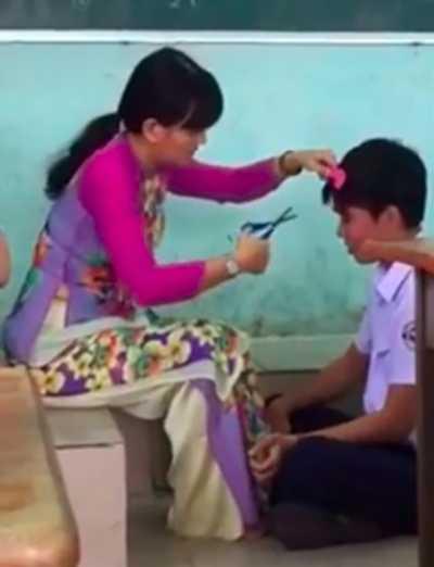 Hình ảnh cô giáo cắt tóc cho học sinh trên bục giảng gây nhiều tranh cãi.