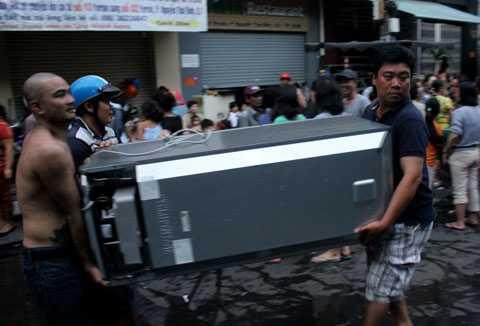Người dân di chuyển đồ đạc về nhà sau khi đám cháy được khống chế.